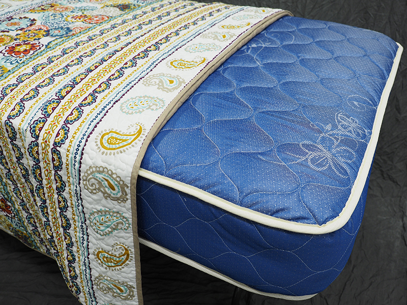 a blue mattress half covered with a quilt